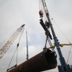 Sea platform legs being hoisted by crane for welding