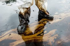 Feet of worker standing in oil spill