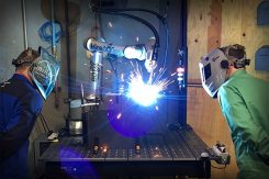 2 welders working with a cobot